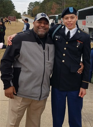 MCH President and CEO stands proudly with alumnus, Kristopher, at his military graduation in 2018. Photo courtesy of MCH